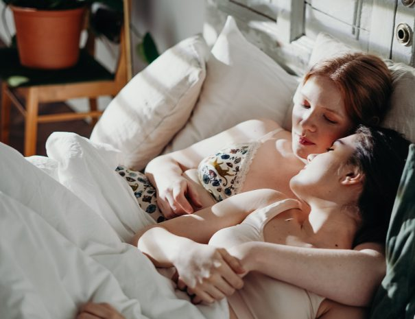 two women relaxing in a hotel bed